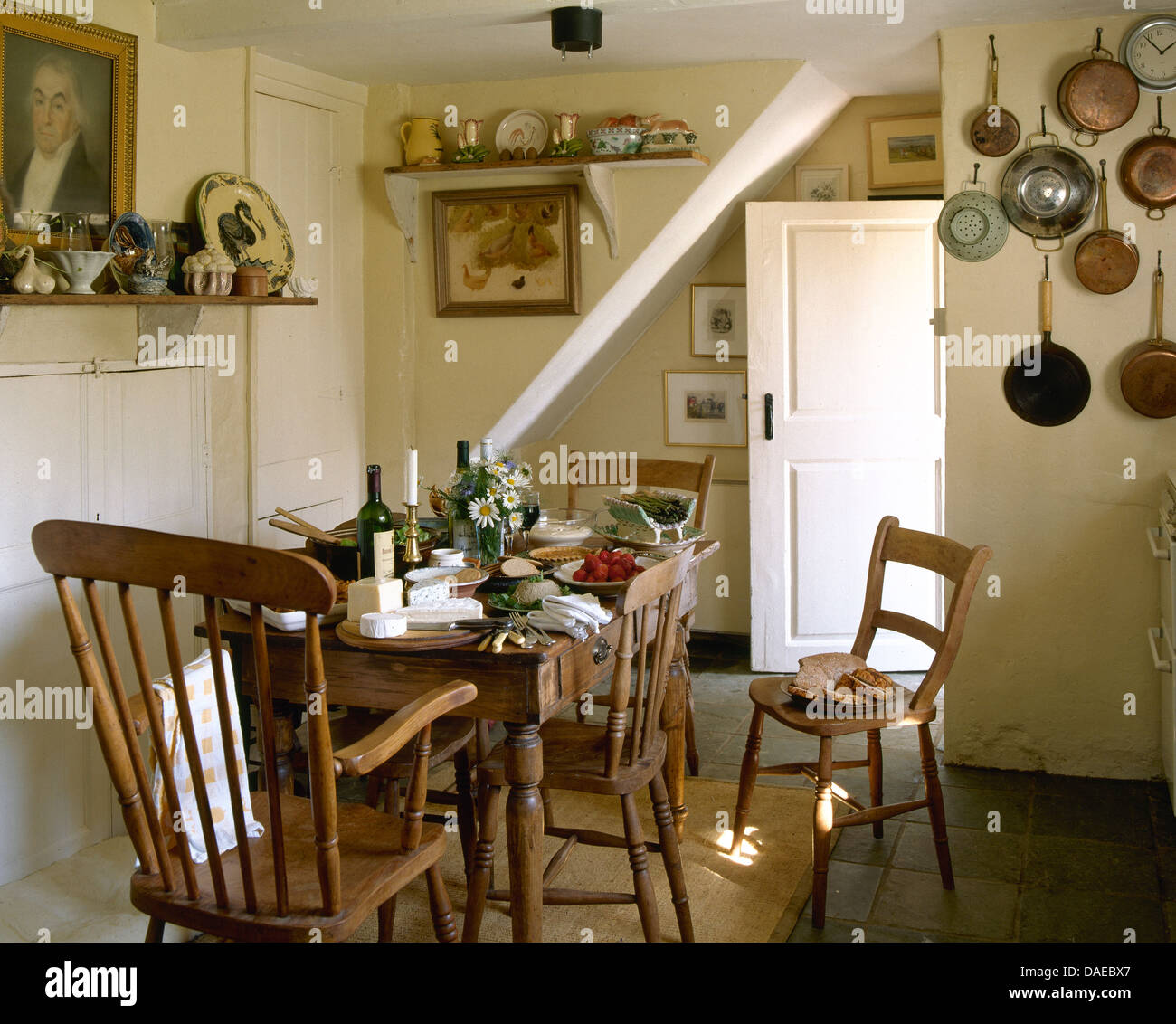 simple wooden chairs and old pine table set for lunch in cottage kitchen DAEBX7