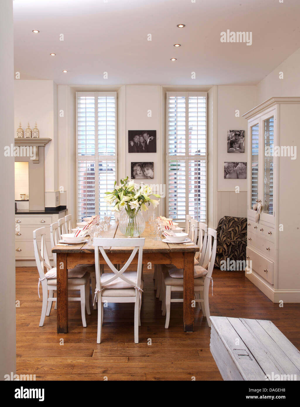 white chairs at simple wood table in modern white kitchen dining room DAGEH8