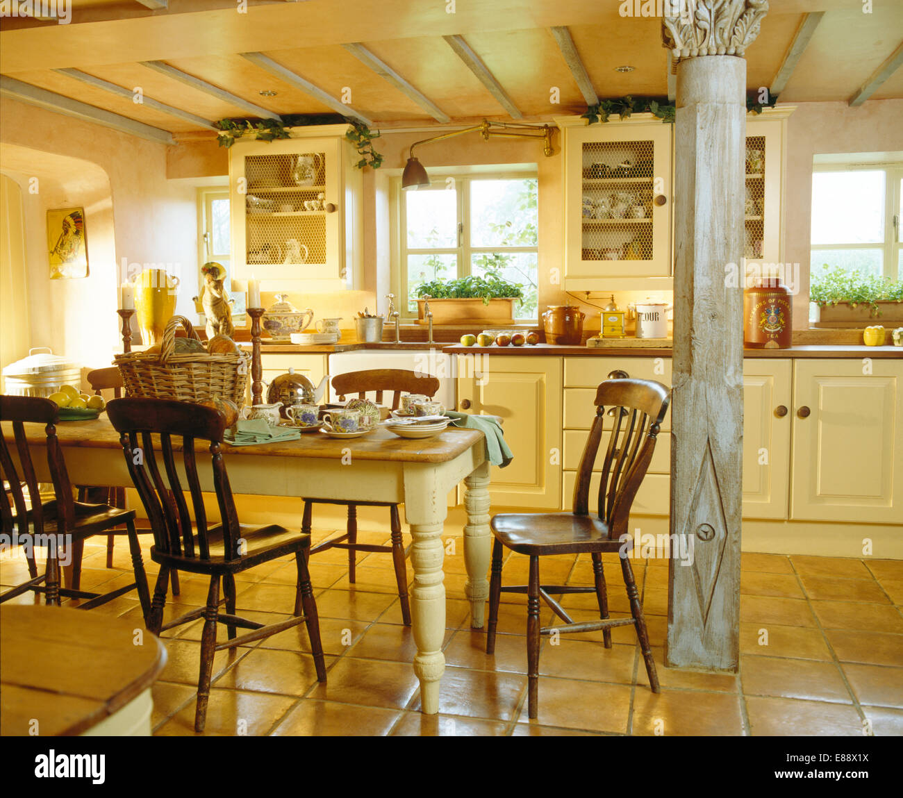 old wooden chairs at painted table in cottage kitchen with classical E88X1X