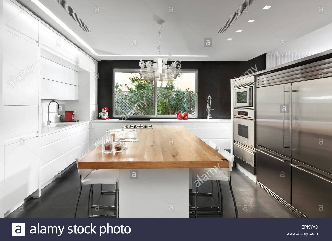 black and white kitchen with wooden dining table in modern villa givat EPKYA0