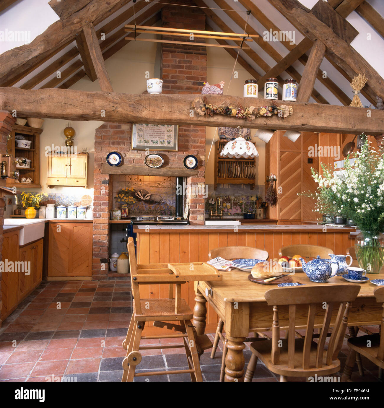 wooden chairs and childs high chair at pine table in barn conversion FB946M