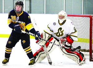 Caledon's Christian Hauck screens Stayner netminder Eric Pitcher during the Hawks' 5-3 win over the Siskins in Caledon East Friday. Photo by Jake Courtepatte