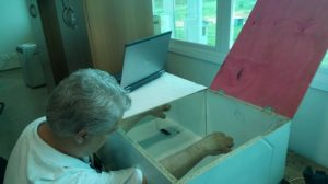 Voluntário do experimento visualizando seu membro fantasma com a reflexão de seu membro remanescente (direito). Foto: Arquivo pessoal