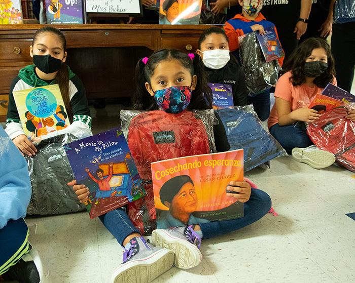 四个学生坐在地板上,戴着面具,展示他们收到的新书
