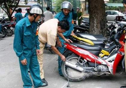 Vietnamese police inspect a scooter apprehended with their net gun. Photo: Vietnamnet
