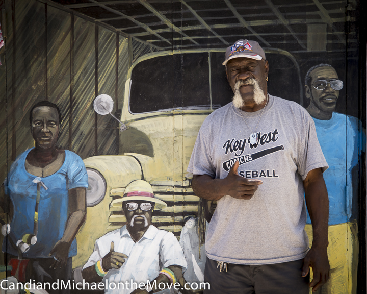 Mr. Chaoman standing in front of a huge mural of all the key people in Bahama Village painted by Rcik Worth
