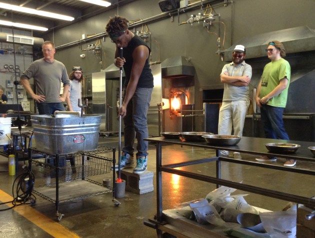 Kedan James demonstrates how to blow glass during one of The Glass Asylum's introduction-to-glass-blowing classes. Photo by The Glass Asylum
