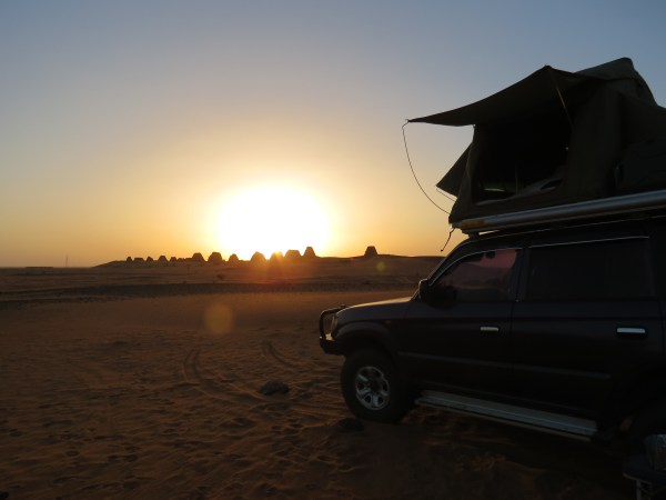 Camping under the desert sky, watching the sun set over the pyramids