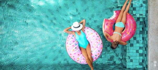 Two people (mom and child) relaxing on donut lilo in the pool at private villa. Summer holiday idyllic. High view from above.