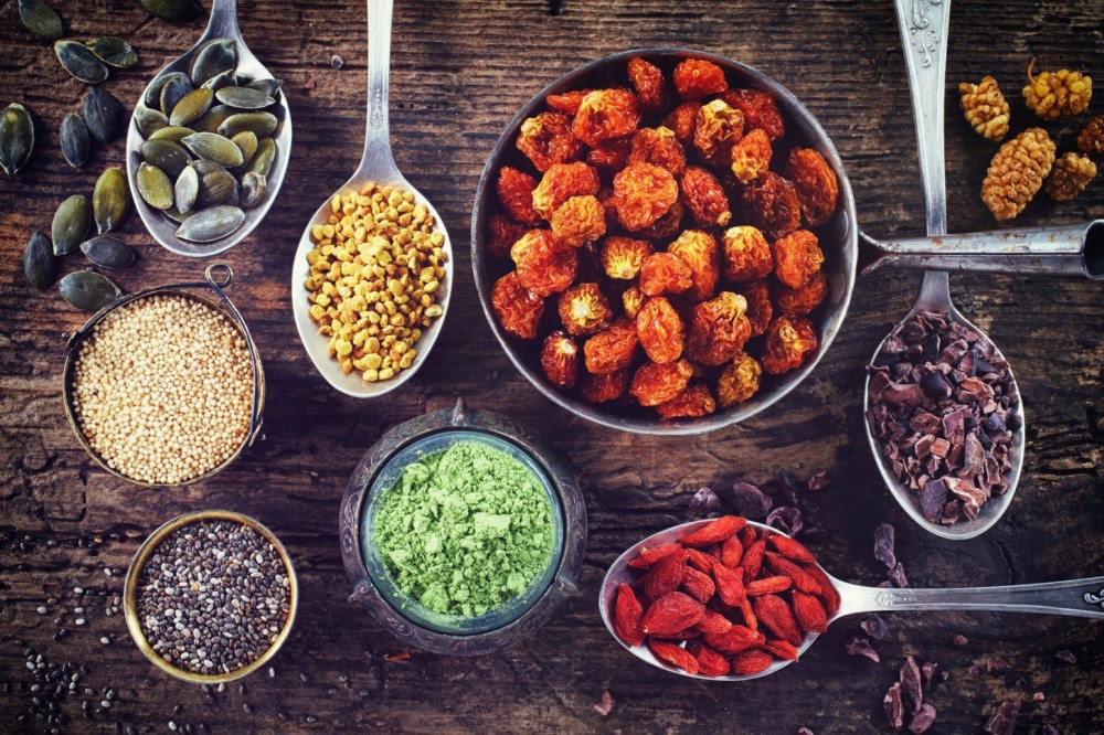 Various superfoods on wooden background