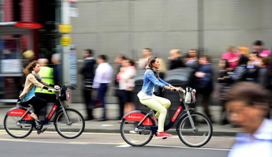 FILE PHOTO - Commuters cycle past a bus queue outside Waterloo Station in London, Britain August 6, 2015. People who commute by bike or on foot have a substantially lower risk of developing cancer or heart disease or dying prematurely, scientists said on Thursday, and governments should do all they can to encourage more active commuting. REUTERS/Dylan Martinez/File Photo