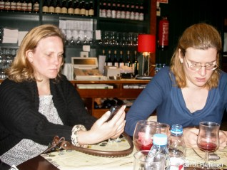 Sarah and Lisa check emails at dinner
