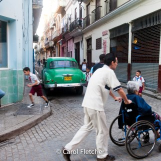 wheelchair elder caretaker street havana cuba