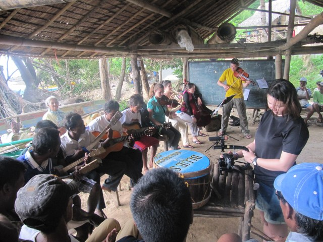 Katrise Velhagen (rightmost, standing) of MAGIS Creative Spaces captures on film the collaboration of Tagbanua and Cultures in Harmony musicians at one of their many community presentations in Culion, Palawan (August 16, 2014)