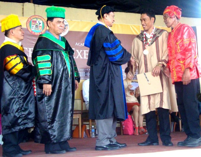 Normindo Mosela (second from right) receives his award while congratulated by State Universities and Colleges President Dr. Perfecto Abilin and other school officials