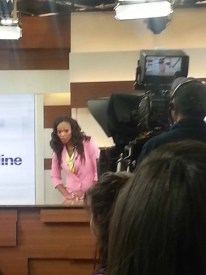 Tracy Moore peeking from behind the camera, joking with the audience at CityLine on April 1, 2013.