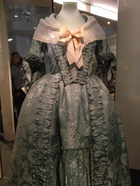 1760s sack-back gown of blue silk damask, trimmed with blue fly fringe