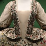 bodice of the 1740s court dress consisting of a white silk mantua robe and petticoat embroidered with polychrome silks and silver threads at the Victoria & Albert Museum in London