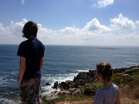 kids watching out onto the Atlantic from the rocky shore along the most westernmost part of N114 in Peniche, Portugal