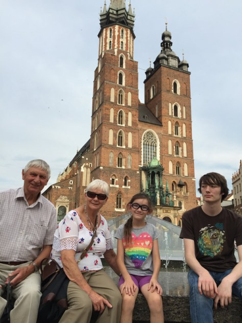 My parents and my kids sitting in front of the St. Mary's Church in the Main Market Square in Krakow, Poland