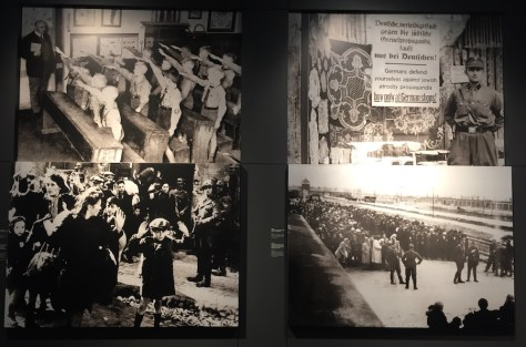 "photo composition from the German Resistance Memorial Center; top left ""Lessons in uniform. Appel, Harburg district, 1933""; bottom left ""Jews after the uprising in the Warsaw Ghetto, prior to their deportation to an extermination camp, May 1943""; top right ""Boycott campaign against Jews, Berlin, April 1, 1933""; bottom right ""Hungarian Jews on the platform at the Auschwitz-Birkenau extermination camp, early Summer 1944."""