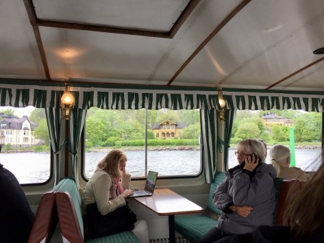 inside view of the Stockholm shuttle ferry (on route 80) with a glimpse on Djurgården island through the windows