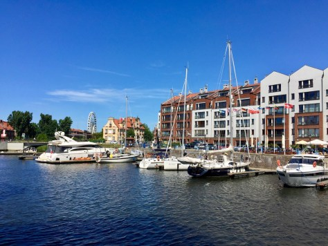 view onto boats in Gdańsk Marina and buildings along Szafarnia Street next to Most Kamieniarski (Stone Bridge) taken from the northernmost tip of the Granary Island