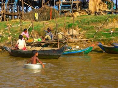 menino usando bacia de barco vila flutuante