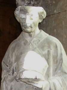 detail of a photograph of a statue of Saint Nicasius of Rheims, Collégiale d'Écouis; taken by Theoliane on 14 October 2007; swiped off the Wikipedia web site