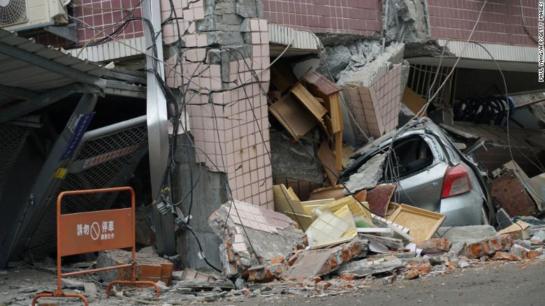 A car sits crushed under a building after a 6.4 magnitude quake hit in Hualien.