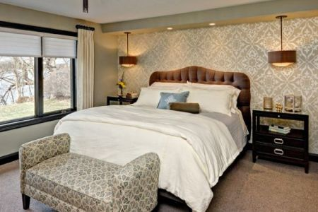 master bedroom with a king sized bed and a bench with fun pattern
