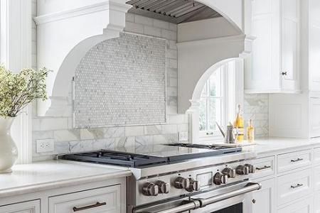 white curved kitchen hood white corbels white mosaic marble stove backsplash
