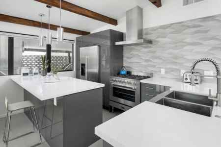 contemporary kitchen with gray cabinets white countertops metallic backsplash and exposed wood beams