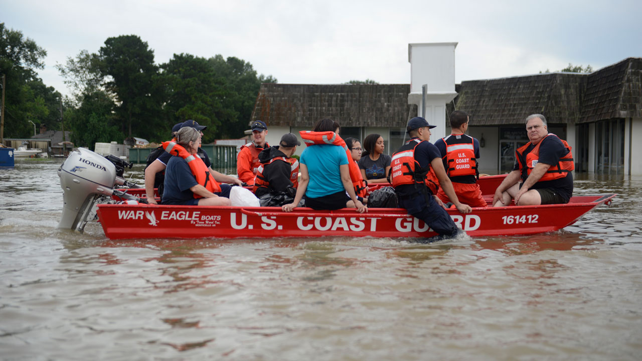 This August 14, 2016 US Coast Guard handout photo shows Coast Guard personel evacuating people from a floodwaters in Baton Rouge, Louisiana. Emergency crews in flood-devastated Louisiana have rescued more than 20,000 people after catastrophic inundations that left at least five dead, news reports said August 15. As many as 10,000 people are living in shelters after a weekend of torrential rains that has prompted the federal government to declare a disaster, according to Louisiana governor John Bel Edwards. Petty Officer 3rd Class Brandon GILES / US Coast Guard / AFP