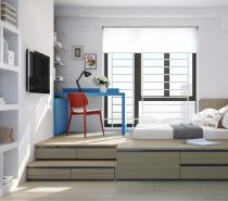 This youngster's room encourages study with a bright desk in primary colors. Drawers expand the functionality of the bed platform, raising the main bedroom area up to window-level.