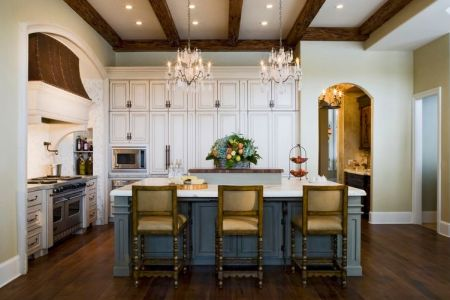 french country kitchen with island and chandeliers above
