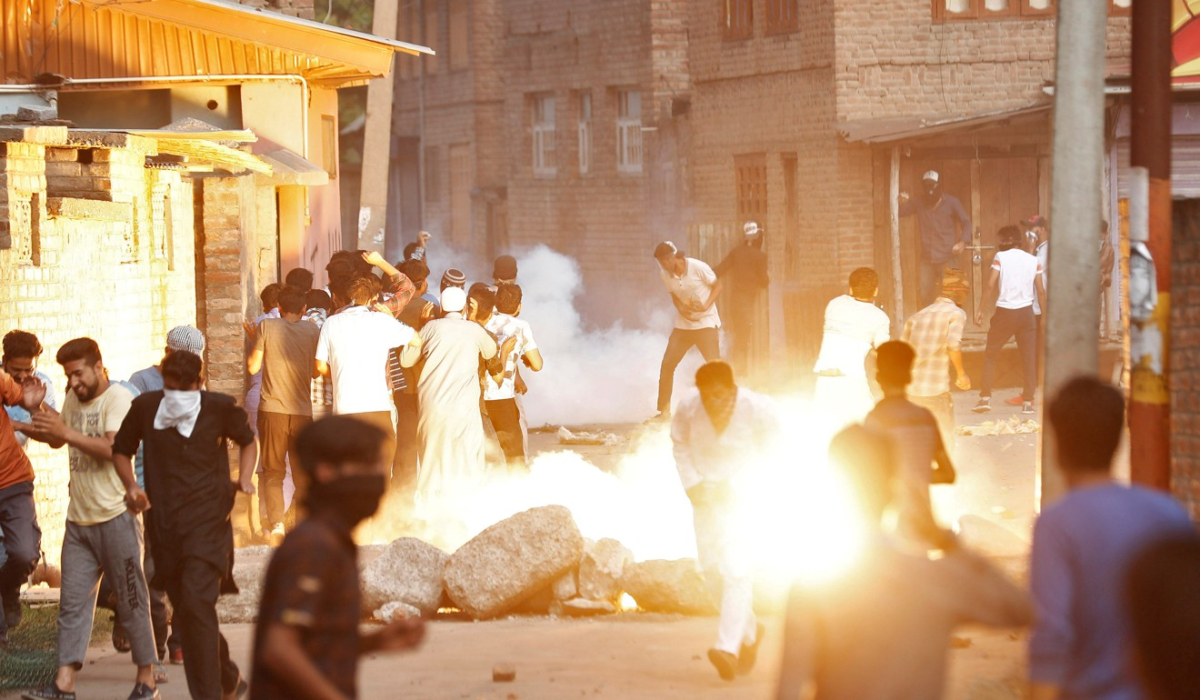 Kashmiris run for cover as a tear gas shell fired by Indian security forces explodes on August 23. Photo: Reuters