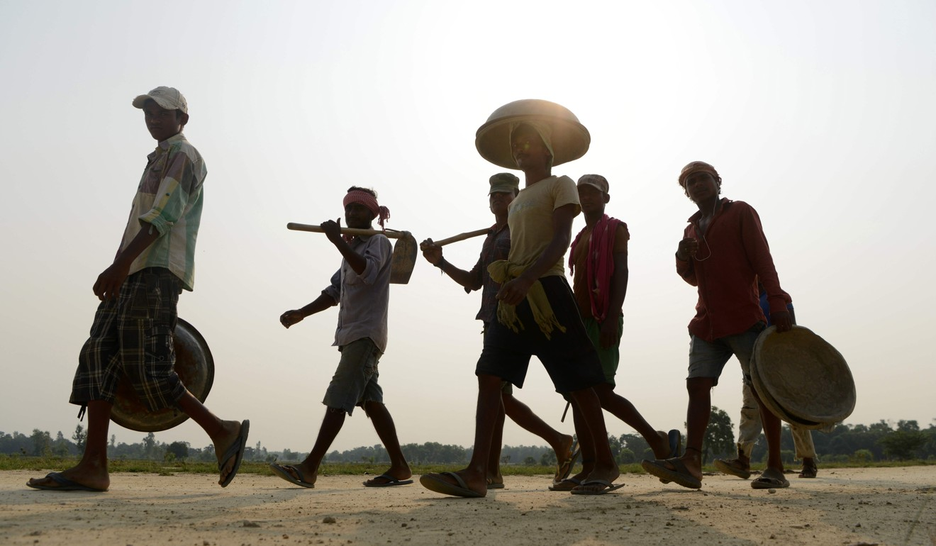 Labourers walk near the construction area of a new railway in Janakpur, some 300km south of Kathmandu. Photo: AFP