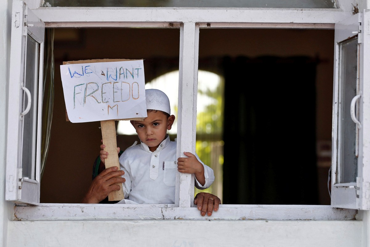 A Kashmiri boy displays a placard from a window at a protest site after Friday prayers. Photo: Reuters
