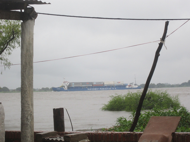 A barge makes its way down the Paraguay river, one of South America's most important rivers, past the town of Villeta, which has several public and private ports and an industrial park that has become the hub of agroindustry in Paraguay, focused on processing soy, of which this small country is one of the world's leading exporters. Credit: Mario Osava/IPS