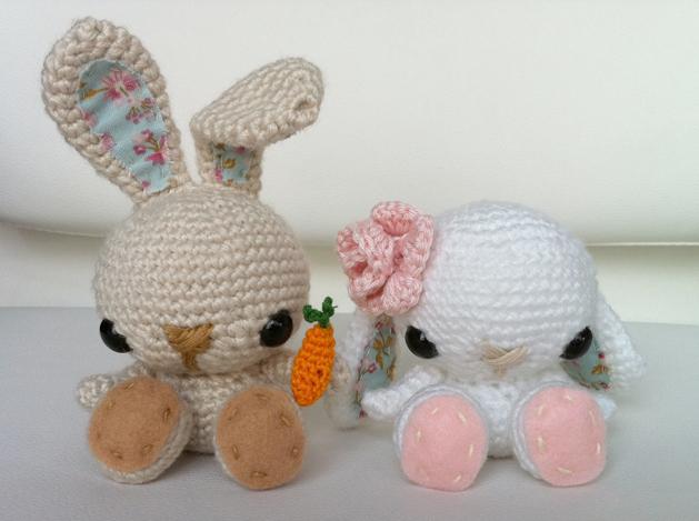 due adorabili coniglietti amigurumi con una carota in mano