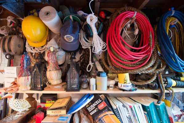 Wall opposite the workbench -- air hoses, extension cords, tow chains, shop manuals, batteries, hardhat and many more useful items carefully hidden in the clutter.