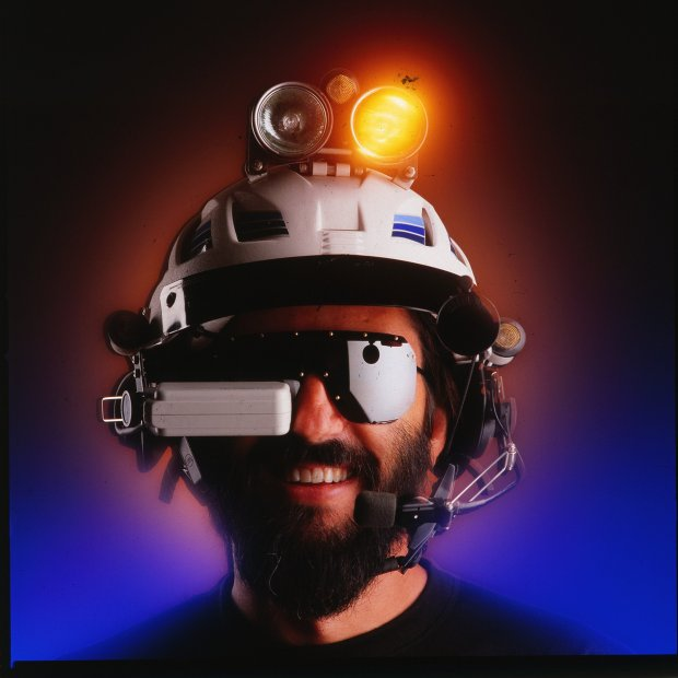 "Steve Roberts and the ""Brain Interface Unit"" for his nomadic ""BEHEMOTH"" bike project. The BIU offered a heads-up data display (via The Private Eye), a head-gesture-controlled mouse, radio communications and entertainment audio, spot and flood lights, a rear view mirror, and even a helmet liquid cooling system."