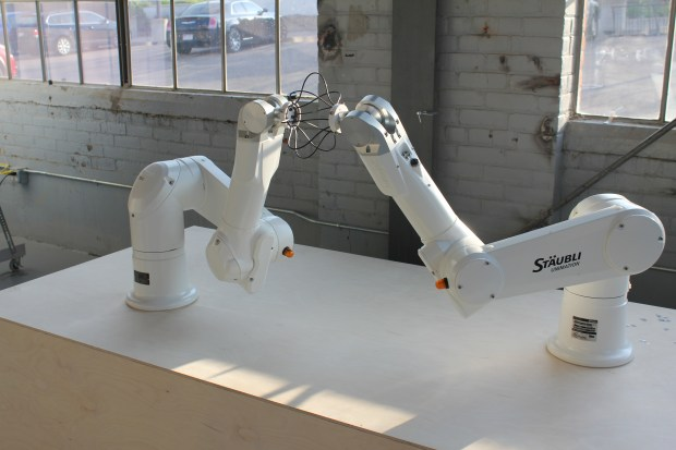 Robot arms deforming a rubber work piece