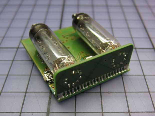 The Numitron tubes connected to the angled PCB boards. Note the side button for changing the time.