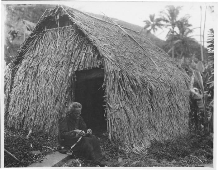 7) A woman sewing lauhala strips into a hat with a grass house in the background, circa 1915.