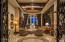 View of formal living from double iron door entry with beautiful wood beamed ceiling