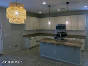 Spacious Kitchen with large island, granite, and stainless steel.