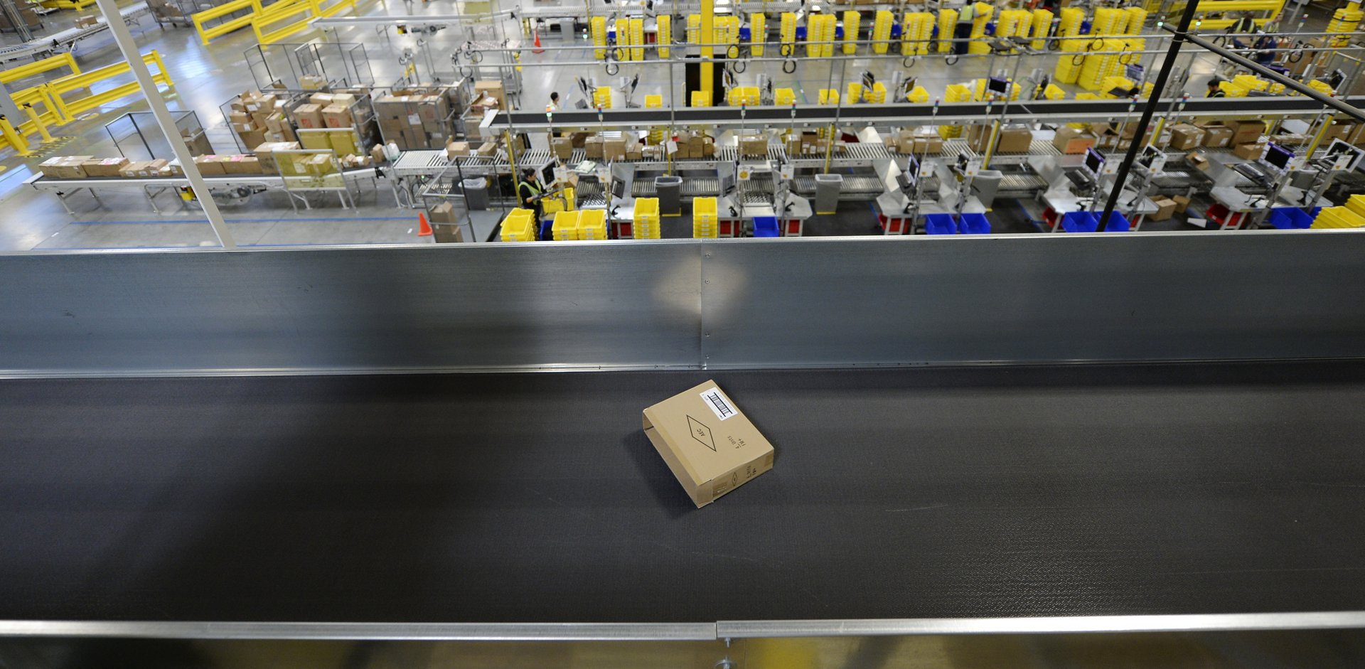 When Amazon Opens Warehouses   The Atlantic A cardboard box on a conveyor belt