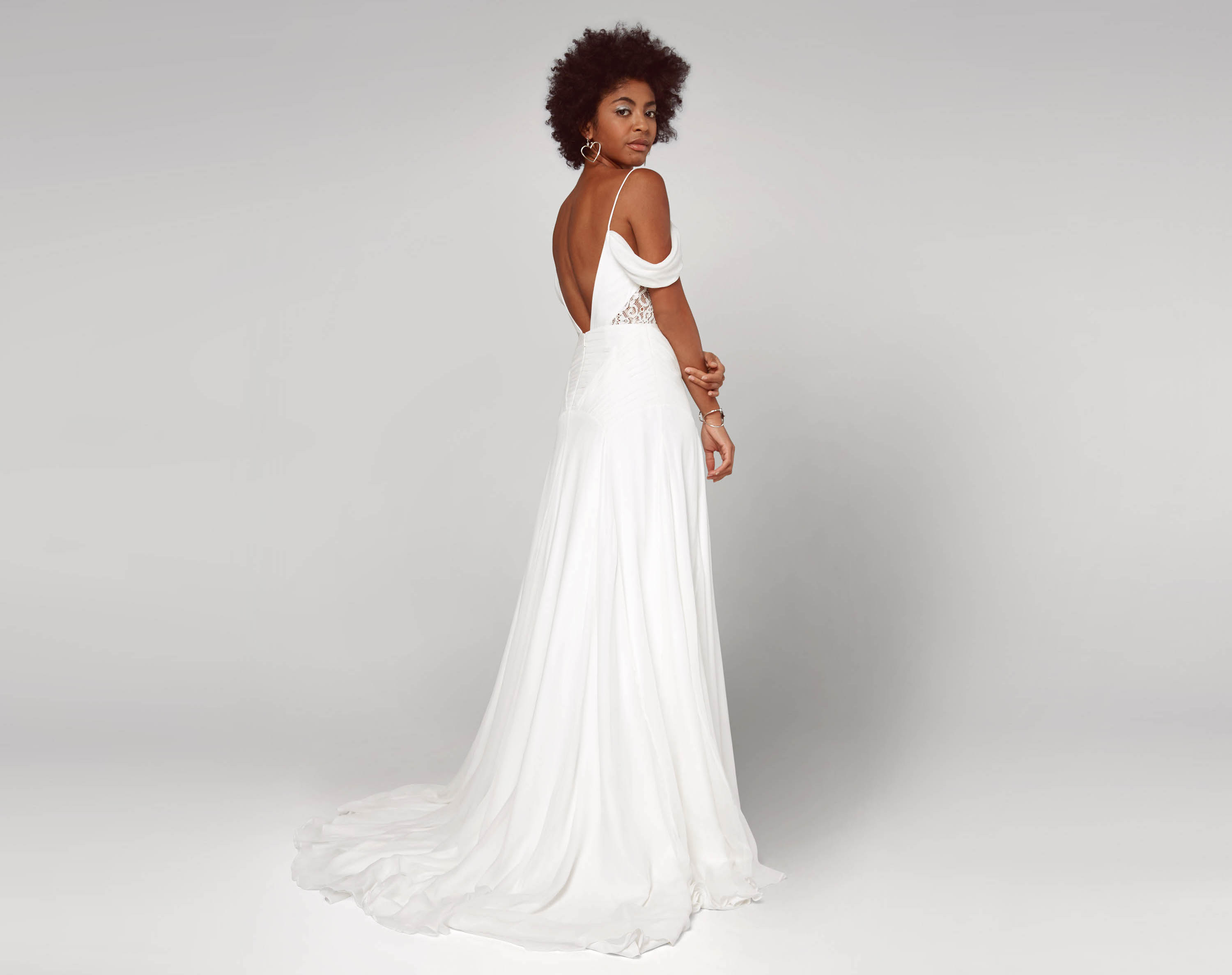 cheap wedding dresses fame partners bridal inexpensive wedding dresses A model wearing a white wedding gown with an open back thin straps and
